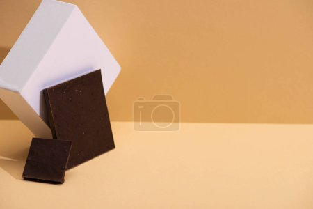 Photo for Delicious dark chocolate pieces and cube on beige background - Royalty Free Image