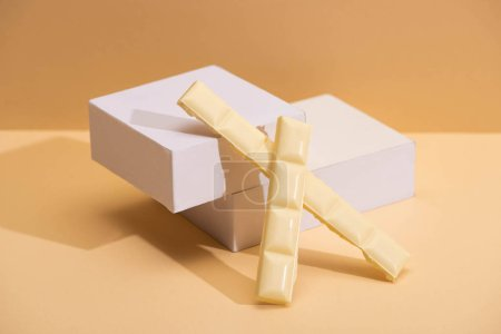 delicious white chocolate pieces and cubes on beige background