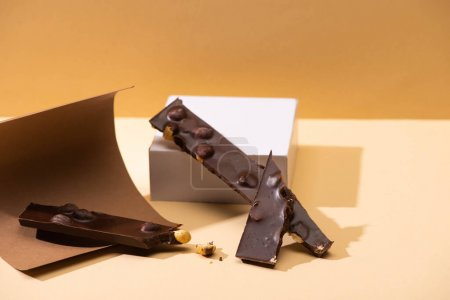 Photo for Delicious dark chocolate with nuts pieces, paper and cube on beige background - Royalty Free Image