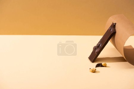Photo for Delicious dark chocolate with nuts piece and paper on beige background - Royalty Free Image