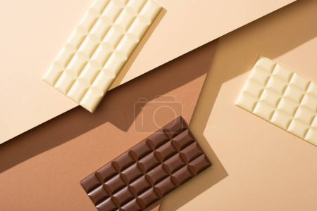 Photo for Top view of delicious whole white and milk chocolate bars on beige background - Royalty Free Image