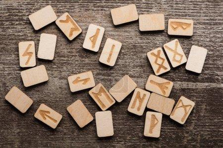 Photo pour Vue de dessus des runes en bois avec des signes ethniques sur la surface en bois - image libre de droit