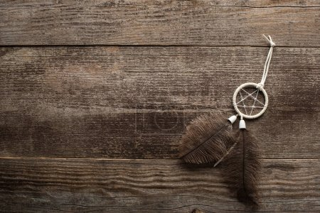 Photo for Top view of dreamcatcher with feathers on wooden background - Royalty Free Image