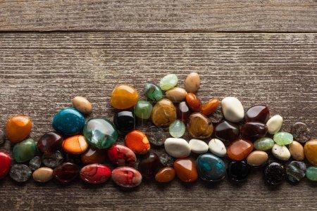 Photo pour Vue de dessus de la fortune colorée racontant des pierres sur la surface en bois - image libre de droit