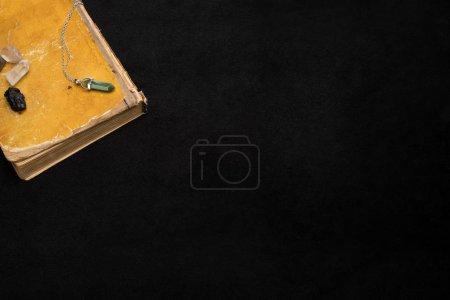 Photo pour Cristaux magiques sur livre isolé sur noir - image libre de droit