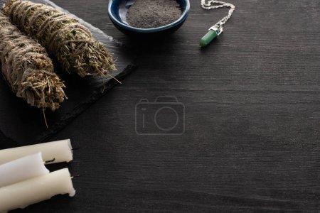 Photo pour Bougies, bâtonnets avec cristal et bol de cendres sur une surface en bois sombre - image libre de droit