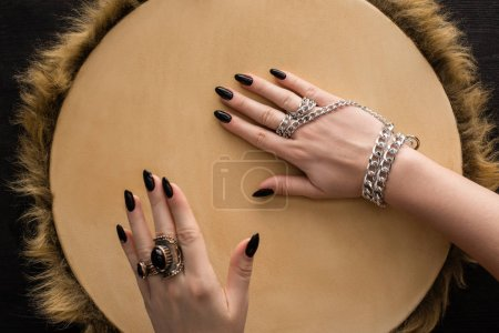 Photo pour Vue du dessus du chaman avec des bagues à bijoux et une chaîne sur les mains jouant sur le tambourin isolé sur noir - image libre de droit