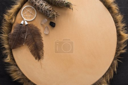 Photo pour Vue du haut des bâtons de purification par la fumée, des cristaux et du capteur de rêves sur tambourin sur fond de bois foncé - image libre de droit
