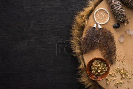Foto de Vista superior de palos de manchas cerca de atrapasueños con plumas y cristales en pandereta chamánica en la superficie de madera oscura - Imagen libre de derechos