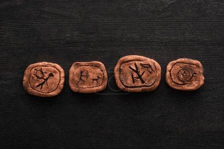 Photo pour Vue de dessus des amulettes d'argile avec des symboles sur fond en bois noir - image libre de droit