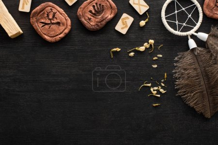 Photo for Top view of runes, dreamcatcher and dry flowers on dark wooden surface - Royalty Free Image