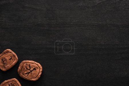 Photo pour Vue du dessus des amulettes d'argile avec des symboles sur fond en bois noir avec espace de copie - image libre de droit