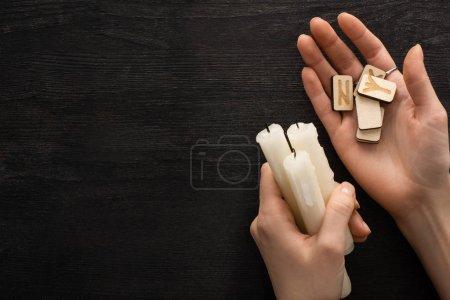 Photo pour Vue du dessus du chaman tenant runes et bougies près du fond en bois sombre - image libre de droit