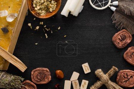 Foto de Vista superior del marco de amuletos chamánicos, libros y velas sobre fondo de madera negra. - Imagen libre de derechos