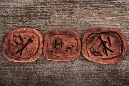 Photo pour Vue du dessus des talismans d'argile avec des symboles sur fond en bois - image libre de droit