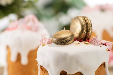 Photo for Close up view of delicious easter cake with golden french macaroons - Royalty Free Image
