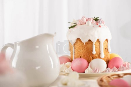 Photo for Delicious Easter cake decorated with meringue with pink and white eggs on plate near jug - Royalty Free Image