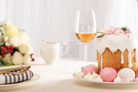 Photo for Selective focus of delicious Easter cake decorated with meringue with pink and white eggs on plate near wine glass and flowers - Royalty Free Image