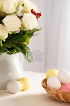 Photo for Vase of fresh flowers on table near colorful Easter eggs in basket - Royalty Free Image