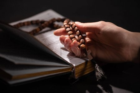 Photo for Cropped view of woman holding rosary with cross near open holy bible in dark with sunlight - Royalty Free Image