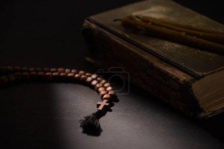 Photo pour Foyer sélectif de la bible sainte avec des bougies et chapelet avec croix dans l'obscurité avec la lumière du soleil - image libre de droit