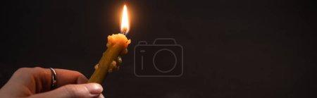 Photo pour Vue recadrée d'une femme tenant une bougie d'église allumée dans l'obscurité, prise de vue panoramique - image libre de droit