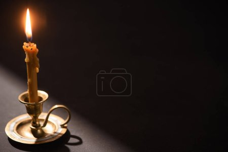 Photo for Church candle in candlestick burning in dark with sunlight - Royalty Free Image