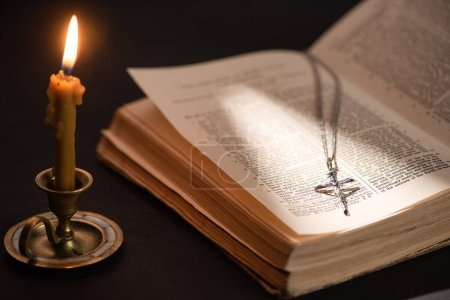 Photo for KYIV, UKRAINE - JANUARY 17, 2020: church candle in candlestick burning near bible with catholic cross in dark with sunlight - Royalty Free Image