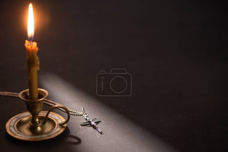 Photo for Church candle in candlestick burning near catholic cross in dark with sunlight - Royalty Free Image
