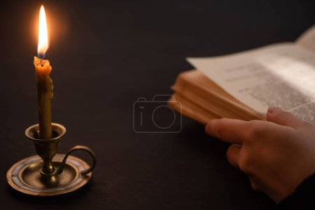 Photo for Cropped view of woman holding holy bible near burning candle in dark - Royalty Free Image