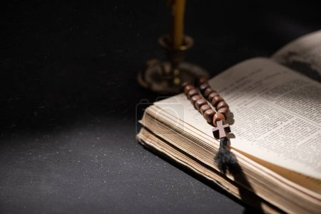 Photo for KYIV, UKRAINE - JANUARY 17, 2020: selective focus of candlestick near bible with catholic rosary in dark with sunlight - Royalty Free Image