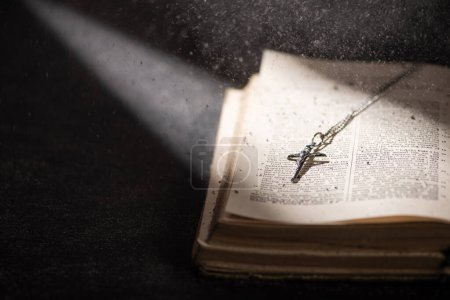 KYIV, UKRAINE - JANUARY 17, 2020: open holy bible with catholic cross and ashes in dark with sunlight