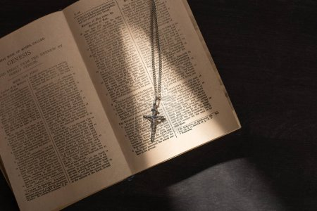 KYIV, UKRAINE - JANUARY 17, 2020: top view of open holy bible with cross on dark background with sunlight