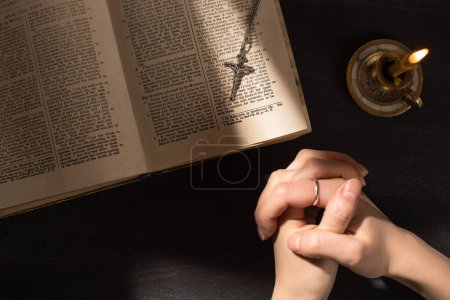 Photo pour KYIV, UKRAINE - JANUARY 17, 2020: cropped view of woman praying near open holy bible with cross on dark background with sunlight - image libre de droit