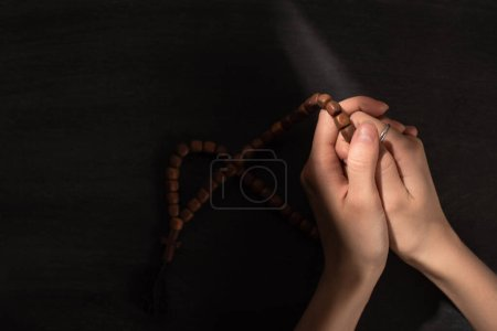 Photo for Cropped view of woman praying with rosary on dark background - Royalty Free Image