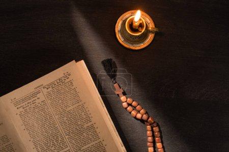 Foto de KYIV, UCRANIA - 17 DE ENERO DE 2020: vista superior de la sagrada biblia abierta con rosario y vela sobre fondo oscuro con luz solar - Imagen libre de derechos