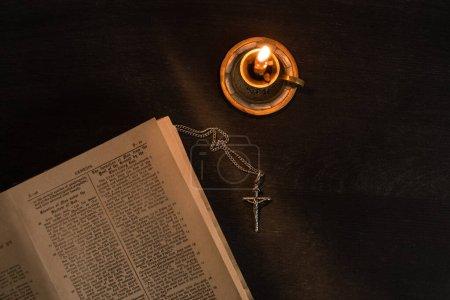 Photo pour KYIV, UKRAINE - 17 JANVIER 2020 : vue de dessus de la bible sainte ouverte avec croix et bougie sur fond sombre - image libre de droit