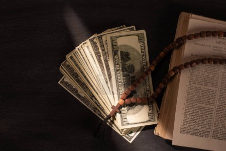 Photo for KYIV, UKRAINE - JANUARY 17, 2020: top view of holy bible with money and rosary on dark background with sunlight - Royalty Free Image