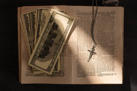 Photo pour KYIV, UKRAINE - JANUARY 17, 2020: top view of holy bible with money and cross on dark background with sunlight - image libre de droit