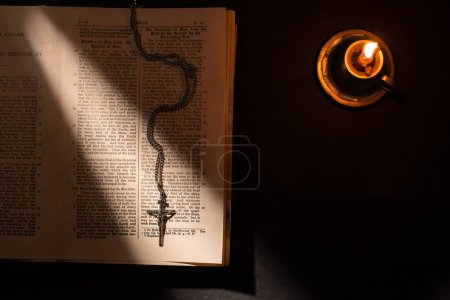 Photo pour Kyiv, Ukraine - 17 janvier 2020 : top view of holy bible with cross and candle on dark background with sunlight - image libre de droit