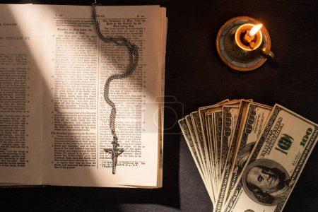 Photo pour KYIV, UKRAINE - 17 JANVIER 2020 : vue de dessus de la bible sainte avec de l'argent, croix et bougie sur fond sombre avec lumière du soleil - image libre de droit