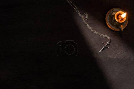 Photo pour Vue du haut de la bougie allumée et croix sur fond sombre avec lumière du soleil - image libre de droit