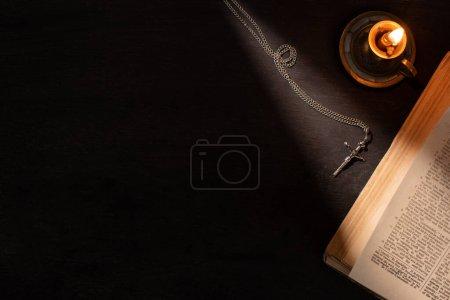 Foto de KYIV, UCRANIA - 17 DE ENERO DE 2020: vista superior de la santa Biblia cerca de la vela encendida y cruz sobre fondo oscuro con luz solar - Imagen libre de derechos