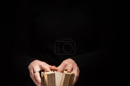 Photo for Cropped view of woman holding holy bible isolated on black - Royalty Free Image