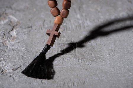 Photo pour Chapelet en bois avec croix sur surface grise texturée - image libre de droit