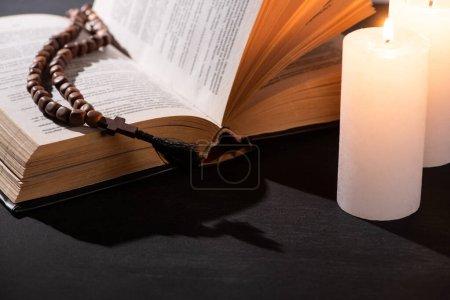 Photo pour Sainte Bible avec chapelet sur fond noir foncé avec des bougies allumées - image libre de droit