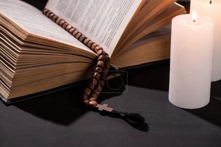 Photo for Holy bible with rosary on black dark background with burning candles - Royalty Free Image