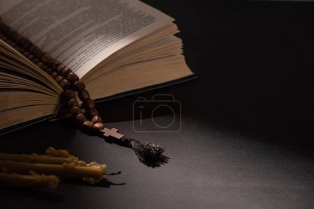 Photo for Holy bible with rosary on black dark background with candles - Royalty Free Image
