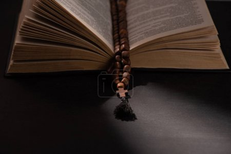 Photo for Holy bible with rosary on black dark background with sunlight - Royalty Free Image