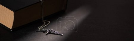 Photo for Holy bible with cross on black dark background with burning candles, panoramic shot - Royalty Free Image